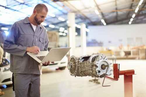 Kfz-Mechaniker mit Laptop in Reparaturwerkstatt